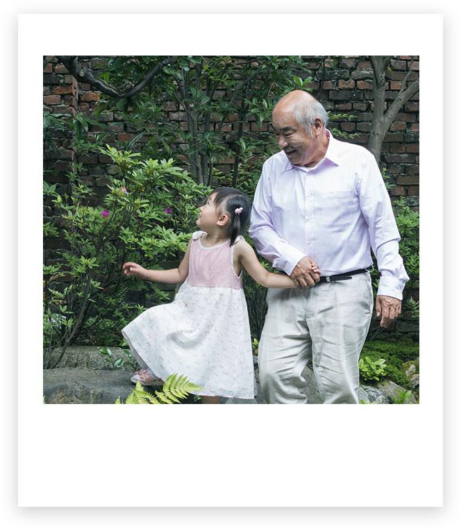 Un grand-père et son petit-fils, main dans la main, à l'extérieur