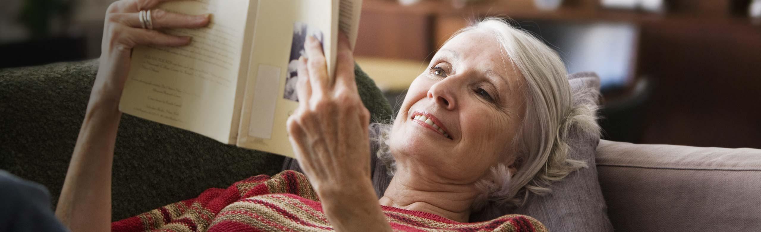 Une femme allongée sur un canapé en train de lire