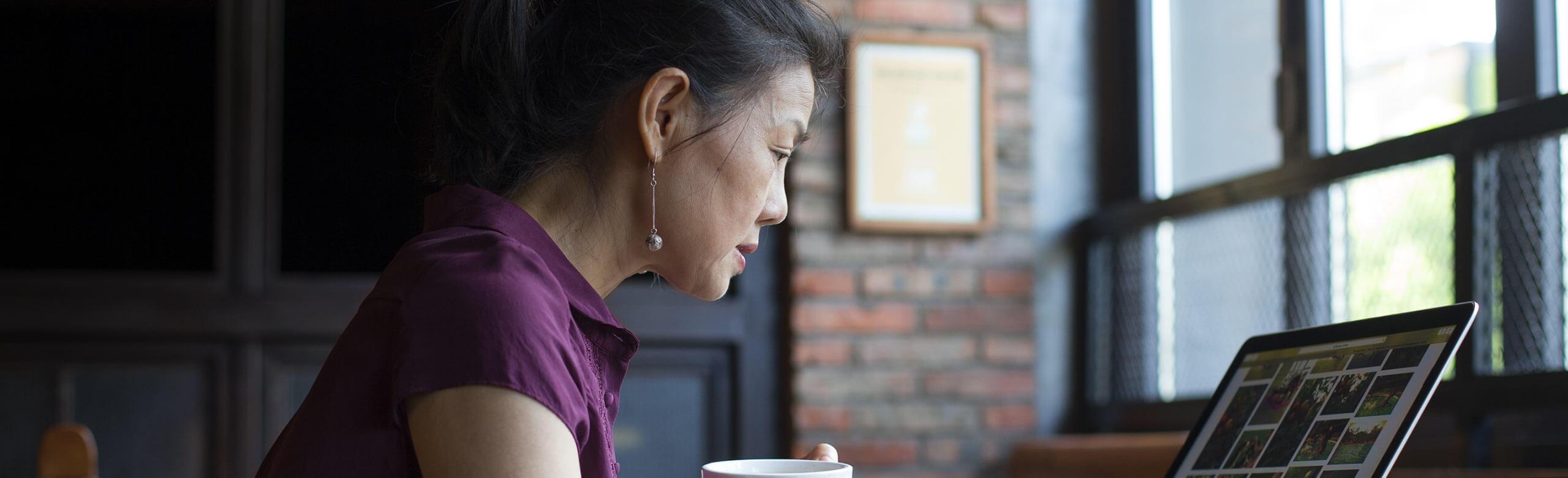 Une femme travaillant sur son ordinateur portable, café à la main