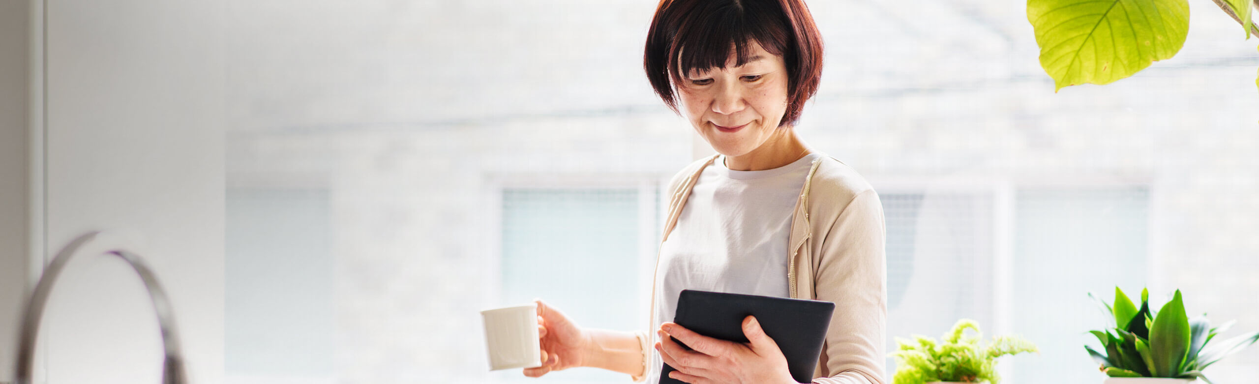 Une femme, café à la main, sur sa tablette