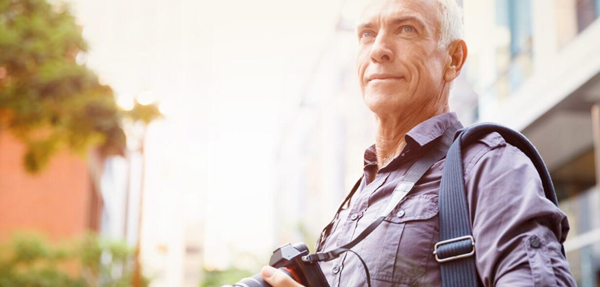Un homme portant son appareil photo autour du cou