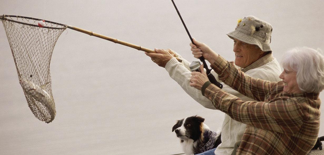 Couple de personnes âgées portant une canne à pêche et une épuisette